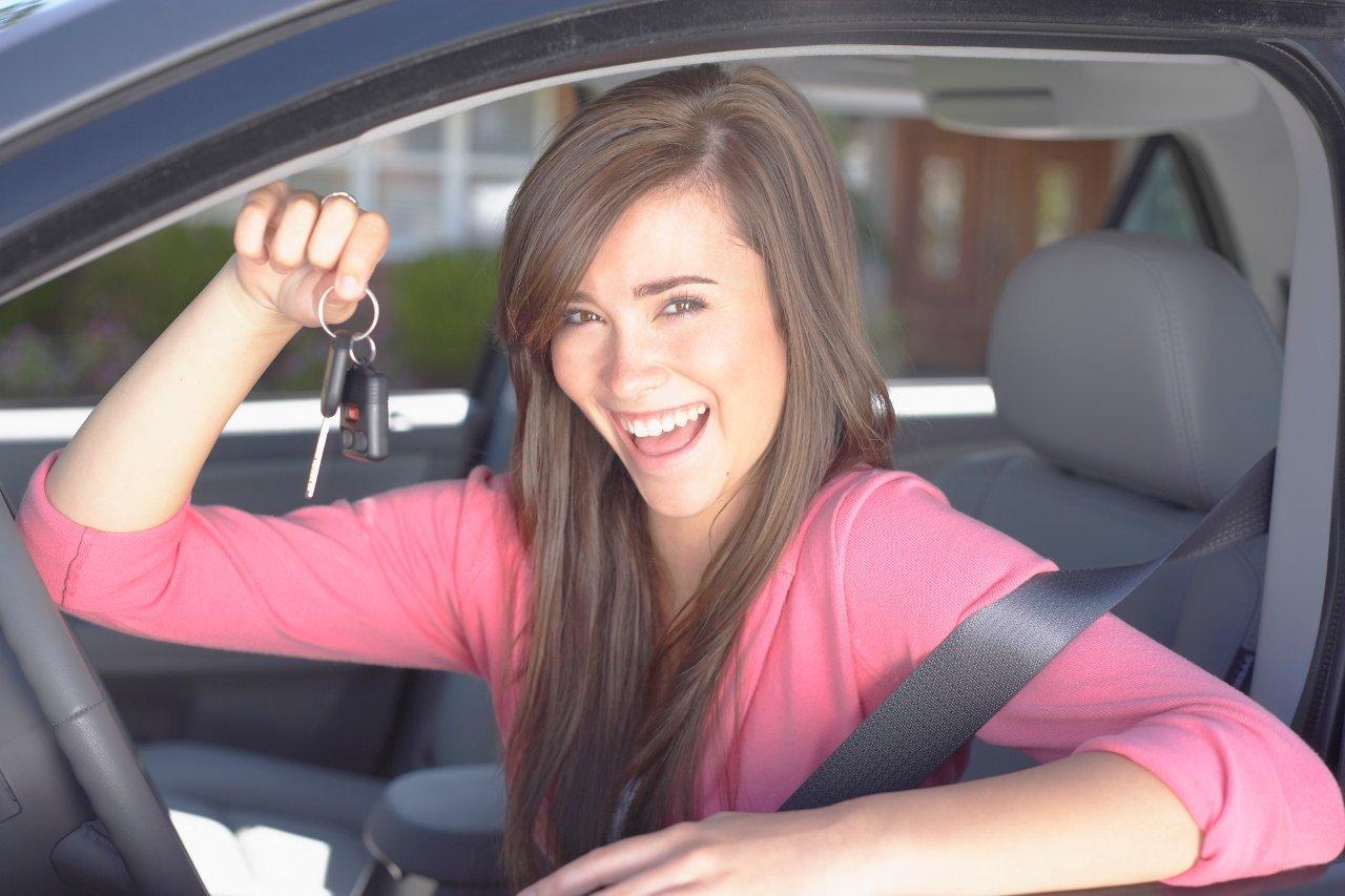 girl at wheel of car, smiling, holding keys