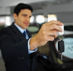 car salesman holding out car key