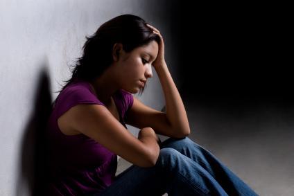 girl sitting in darkened room looking sad